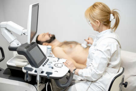 Doctor examining liver of male patient with ultrasound scan in clinic 免版税图像
