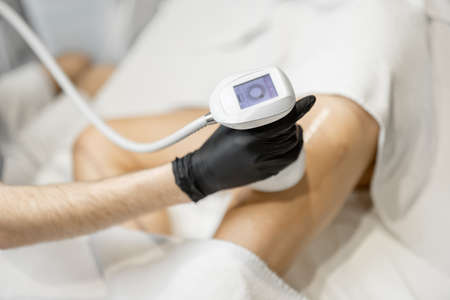 Doctor doing ultrasound liposuction procedure in medical clinic.