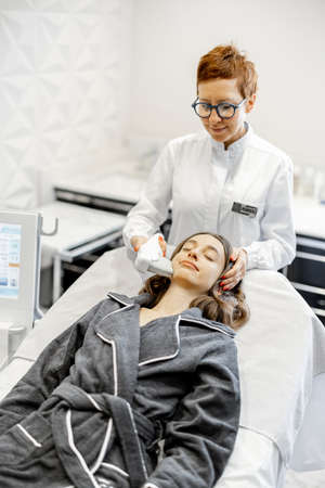 Woman on ultrasound face lifting procedure in cosmetology salon