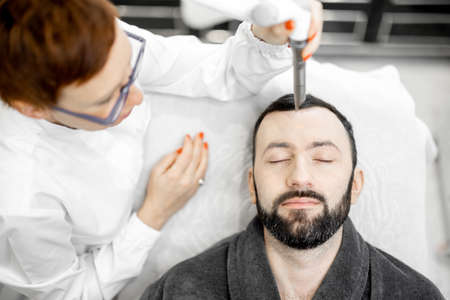Cosmetologist doing laser facelifting procedure in beauty clinic