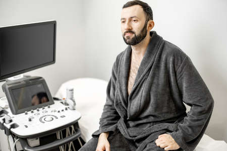 Man waiting for the doctor for ultrasound scan in medical clinic.
