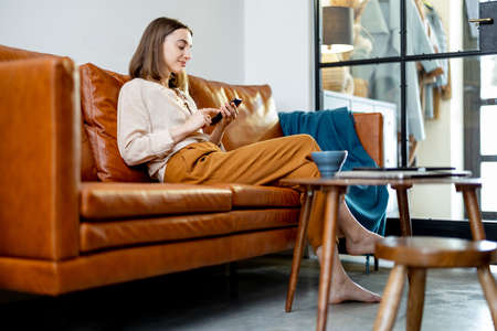Woman sitting on the sofa at home with smartphone