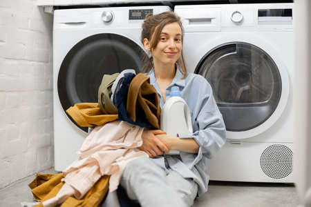 Woman with clean clothes and detergent in the laundry room at home
