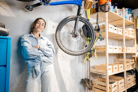 Portrait of a young handywoman standing relaxed in the workshop or garage with bicycle and wooden shelves