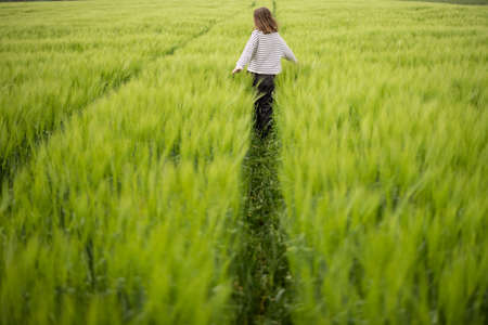 Relaxed woman standing in green field and enjoys calm nature