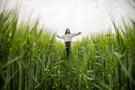 Relaxed woman standing in green field and enjoys calm nature Stock Photo