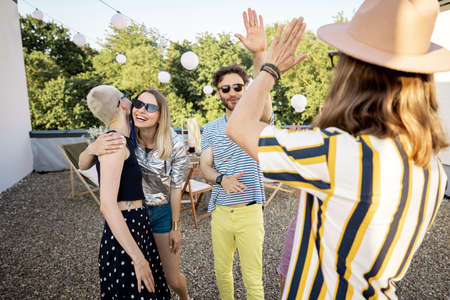 Young stylish friends greets, hugging each other tightly while gathering on a party outdoors. Two hipsters meet on rooftop party