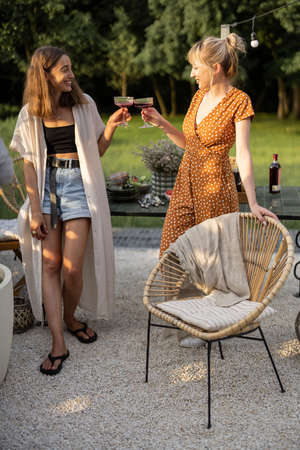 Two girlfriends clinking wine glasses talking and having fun during a lunch at backyard on nature Foto de archivo