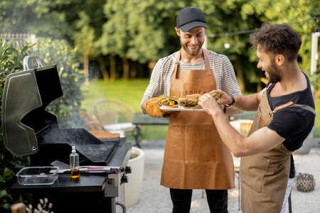 Two handsome male friends have fun while grilling meat and buns for burgers on gas grill at backyard on nature