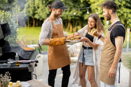 Young people enjoy yummy burgers, made on a grill at picnic, standing together and having fun. Friends cooking at backyard outdoors. American lifestyle