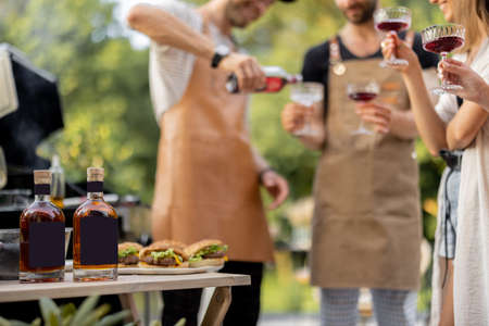 Young people with alcohol drinks at picnic, pouring wine or liqueur into a glasses. Image focused on the bottles at table in front