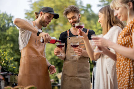 Young people with alcohol drinks at picnic, pouring wine or liqueur into a glasses. Have fun hanging out together outdoors