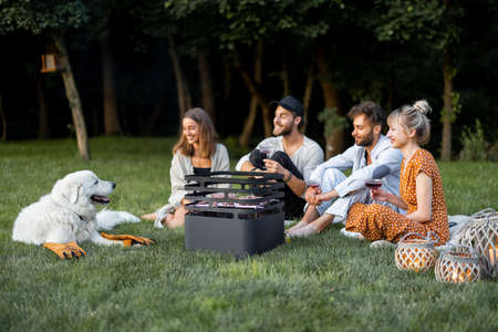 Young friends sitting together by the barbeque with a dog, talking and drinking wine in a close and friendly atmosphere, having a picnic in the evening