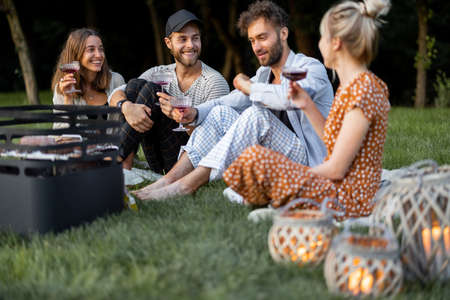 Young friends sitting together by the barbeque, talking and drinking wine in a close and friendly atmosphere, having a picnic in the evening