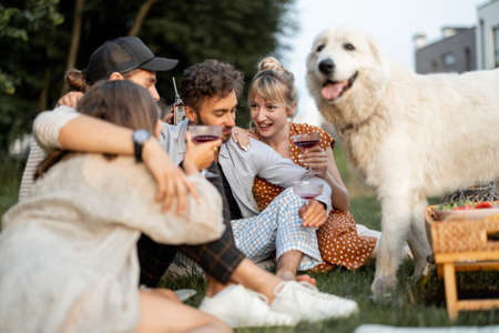 Friends have fun sitting together with a huge dog at picnic on the backyard. on the evening Spending summer time in a small group outdoors Foto de archivo