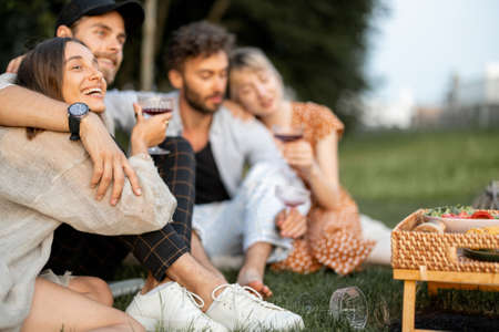Young friends sit together and hug, talk and drink wine in a close and friendly atmosphere on a picnic in the evening Foto de archivo