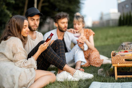 Young friends sit together and hug, talk and drink alcohol in a close and friendly atmosphere on a picnic in the evening