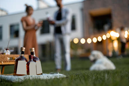 People have fun on the picnic at backyard in the evening, Close-up on bottles in front with blank label to copy paste