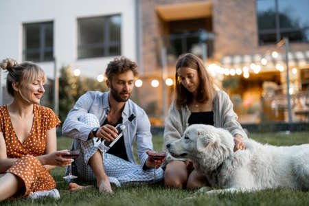 Young friends having fun playing with a dog and drinking wine, sitting on the green lawn at backyard of the country house in the evening