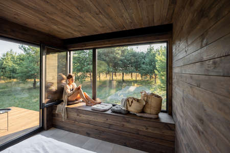 Young woman resting at beautiful country house or hotel, sitting with phone on the window sill enjoying beautiful view on pine forest. Concept of solitude and recreation on nature
