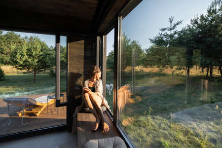 Young woman resting at beautiful country house or hotel, sitting on the window sill enjoying beautiful view on pine forest. Concept of solitude and recreation on nature