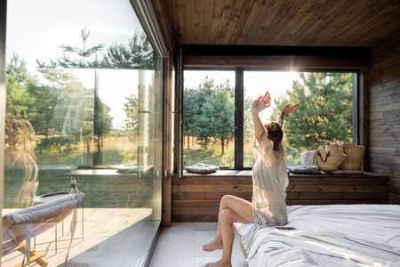 Woman wakes up in a country house or hotel with panoramic windows in pine forest raised her hands yawning. Good morning and recreation on nature concept