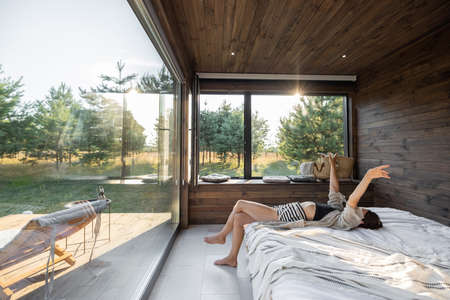 Woman wakes up in a country house or hotel with panoramic windows in pine forest lying on the bed and raised her hands. Good morning and recreation on nature concept