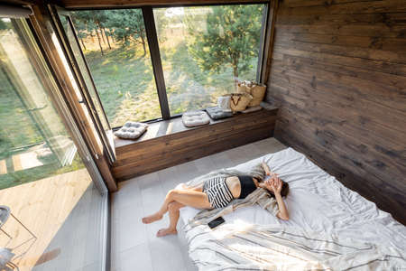 Woman wakes up in a country house or hotel with panoramic windows in pine forest lying on the bed and yawns. Good morning and recreation on nature concept. View from above.