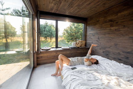Woman wakes up in a country house or hotel with panoramic windows in pine forest lying on the bed and raised her hands yawning. Good morning and recreation on nature concept