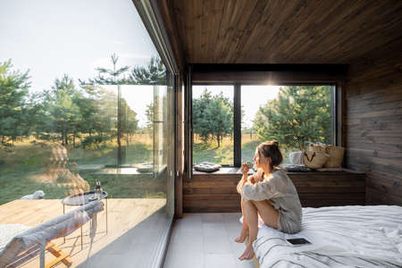Woman in a country house or hotel with panoramic windows in pine forest sitting on the bed and enjoys beautiful view with light sun. Good morning and recreation on nature concept