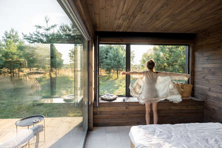 Woman enjoys in a country house or hotel staying with open hands near panoramic windows with pine forest view. Good morning and recreation on nature concept. Back view. Copy Space