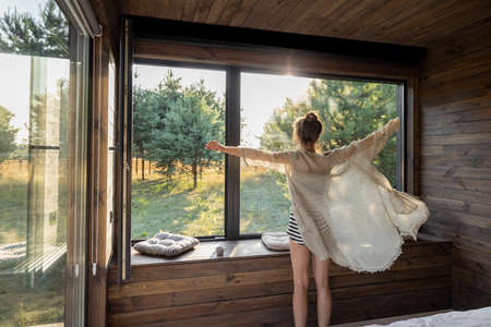 Woman enjoys sunrise in a country house or hotel staying with open hands near panoramic windows with pine forest view. Good morning and recreation on nature concept. Back view Foto de archivo