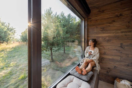 Young woman resting at beautiful country house or hotel, sitting with phone and cup on the window sill enjoying beautiful view on pine forest. Concept of solitude and recreation on nature Foto de archivo
