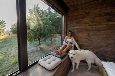 Young woman resting at beautiful country house or hotel, sitting on the window sill enjoying beautiful view on pine forest with big white dog. Concept of solitude and recreation on nature with pet