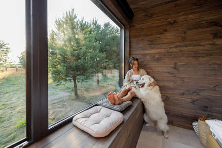 Young woman resting at beautiful country house or hotel, sitting on the window sill with pine forest view and hug a big white dog. Concept of solitude and recreation on nature with pet