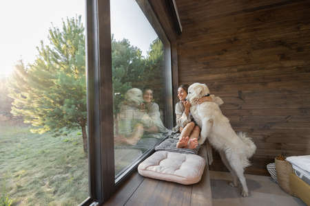 Young woman resting at beautiful country house or hotel, sitting on the window sill with pine forest view and hugs with big white dog. Concept of solitude and recreation on nature with pet