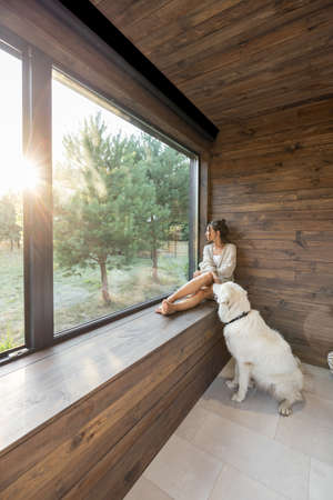 Young woman resting at beautiful country house or hotel, sitting on the window sill with pine forest view while sunrise and white dog sits near. Concept of solitude and recreation on nature with pet Foto de archivo