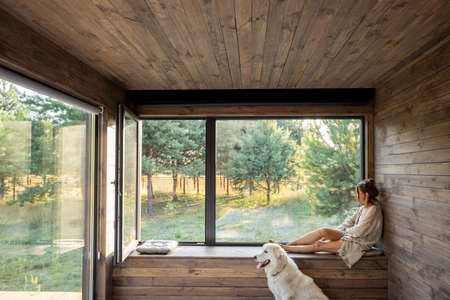 Young woman resting at beautiful country house or hotel, sitting on the window sill with pine forest view and big white dog sits near. Concept of solitude and recreation on nature with pet