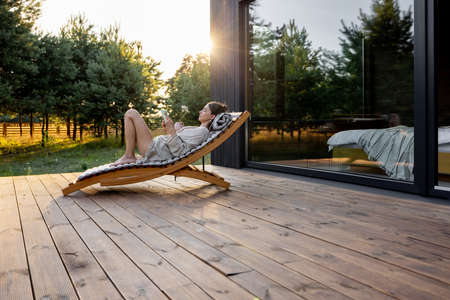 Young woman resting on sunbed and reading on a tablet on the wooden terrace near the modern house with panoramic windows near pine forest. Wellness and mindful health. Copy space Foto de archivo