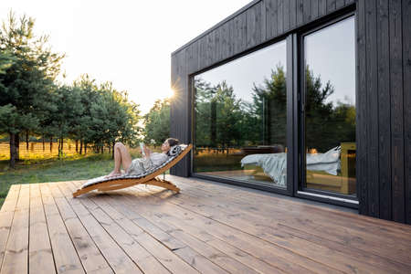 Young woman resting on sunbed and reading on a tablet on the wooden terrace near the modern house with panoramic windows near pine forest. Concept of solitude and recreation on nature Foto de archivo