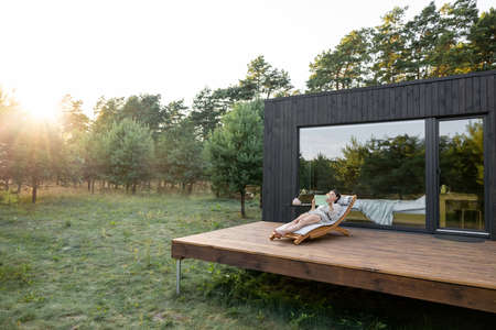 Woman resting on sunbed and reading on a tablet on the wooden terrace near the modern house with panoramic windows near pine forest while sunrise. Concept of solitude and recreation on nature