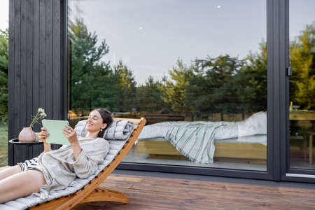 Young woman resting on sunbed and reading on a tablet on terrace at modern house with panoramic windows near pine forest. Concept of solitude and recreation on nature. Wellness and mindful resort