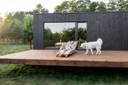 Woman resting on sunbed on the wooden terrace near the modern house with panoramic windows near pine forest with big white dog. Wellness and mindful health. Copy space Foto de archivo