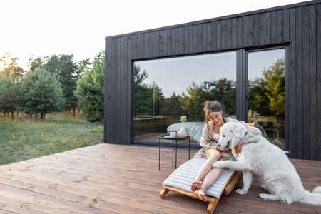 Woman resting on sunbed on wooden terrace near the modern house with panoramic windows near pine forest while playing with pet. Concept of solitude and recreation on nature