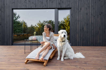 Woman enjoys the nature while sits on sunbed on wooden terrace near the modern house with panoramic windows near pine forest whith big white dog. Concept of solitude and recreation on nature Foto de archivo