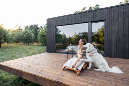 Woman enjoys the nature while sits on sunbed on wooden terrace near the modern house with panoramic windows near pine forest while hugs her pet. Concept of solitude and recreation on nature