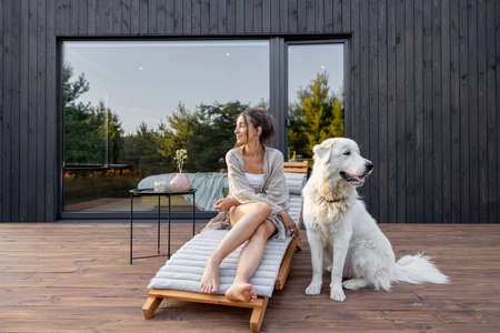 Woman enjoys the nature while sits on sunbed on wooden terrace at the modern hotel resort with panoramic windows near pine forest whith big white dog. Concept of solitude and recreation on nature