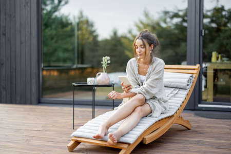 Young woman resting on sunbed and looks on the phone on terrace at modern house with panoramic windows near pine forest. Concept of solitude and recreation on nature. Wellness and mindful resort.