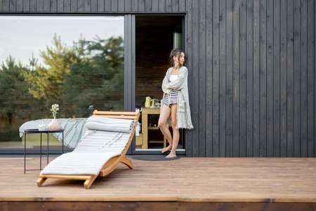 Young woman staying on terrace of wooden modern house with panoramic windows near pine forest. Concept of solitude and recreation on nature. Wellness and mindful resort. Beautiful place for vacation.