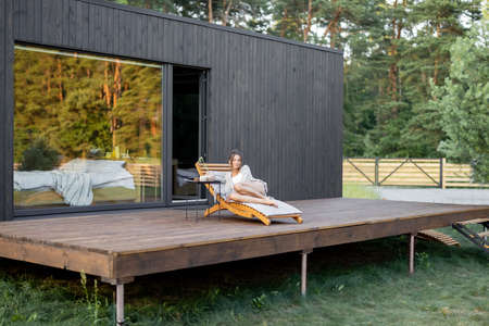 Young woman resting on sunbed on big terrace of modern wooden house with panoramic windows near pine forest. Wellness and mindful resort. Beautiful place for vacation Foto de archivo